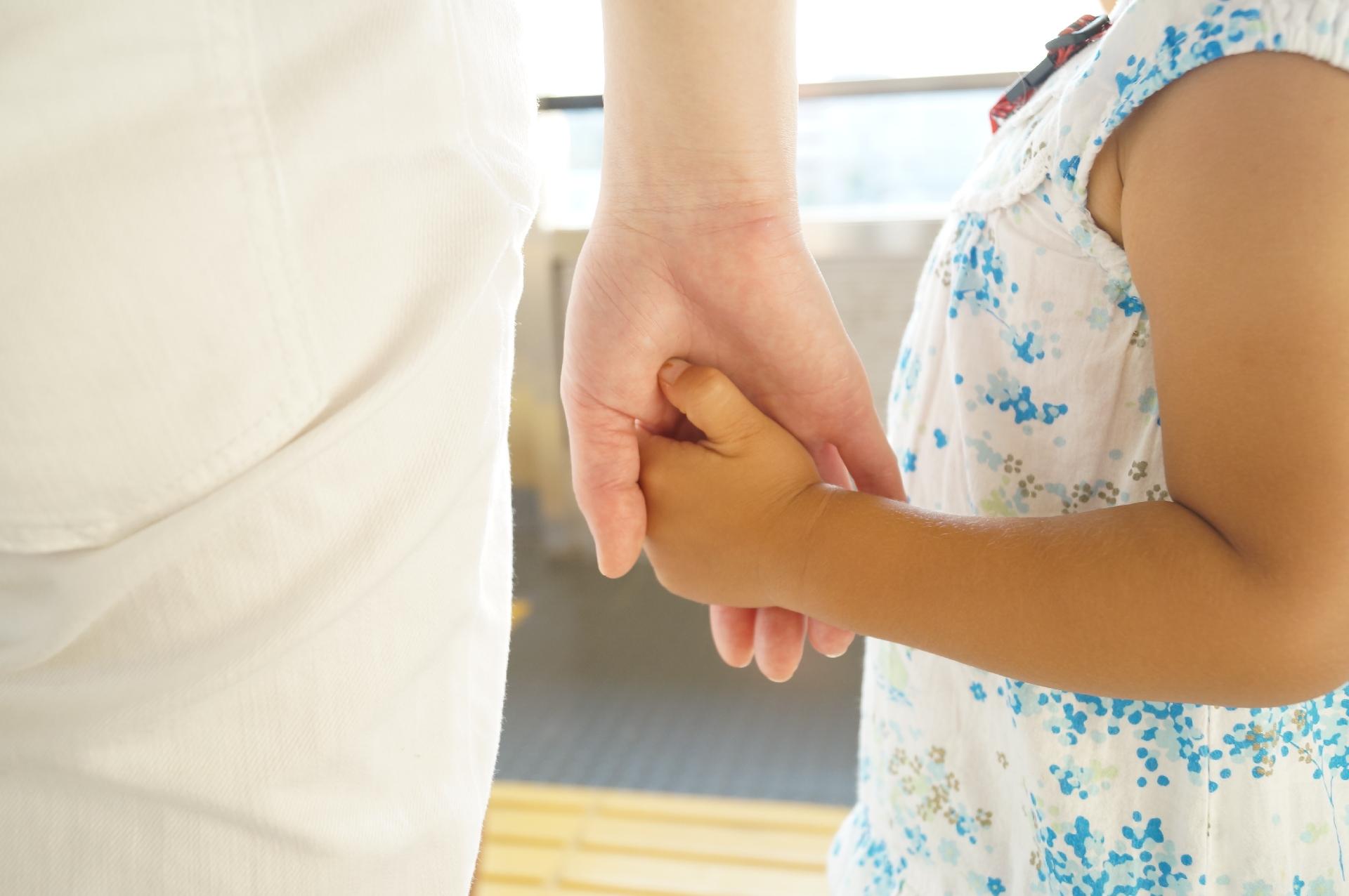子どもの手を握る大人